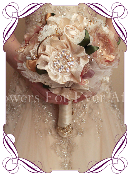 Vintage glamour elegant silk bridal design. Features all hand made fabric flowers, each set with brooches. Fabrics used are in ivories, creams, champagnes, dusty pinks, apricots and golds, with scattered gold wired diamante crystals, gold metal loops and laces. The handle is wrapped in a cream satin with detailing in lace and brocade with light gold leaves and pearls. brooch bouquet, bling bouquet