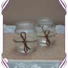 Small rustic jars decorated with lace and ribbon and baby's breath. Wedding table decoration for a rustic theme. Tea light candle votive
