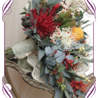 Australian native silk artificial wedding bouquet in traditional desert colours with red, orange and yellow with gum leaves. Cascading tear bridal bouquet