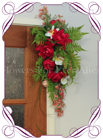 Vibrant tropical silk artificial arbor decoration with red and coral pink peonies, frangipani and ferns. Colourful / colorful wedding arbor / arch tie back decoration