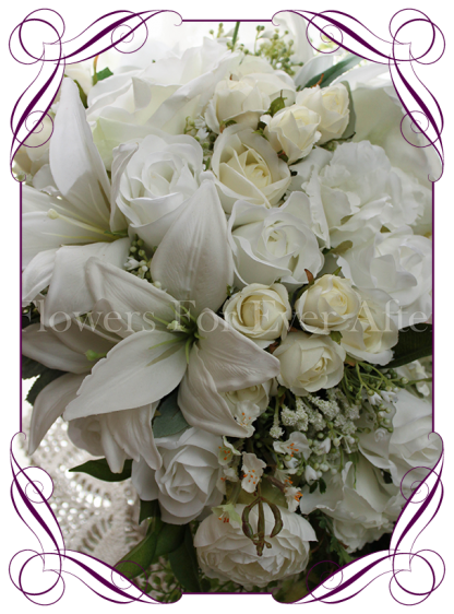 Silk artificial white classic elegant tear bridal bouquet with roses, peonies, lilies, ranunculi, baby's breath and fine foliage.