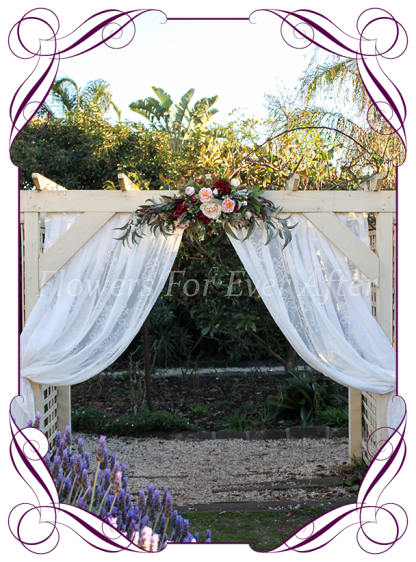 Silk faux flower wedding arbor arch corner decoration florals featuring silk roses in burgundy and apricot and native gum leaves foliage. Made in Melbourne by Australia's best silk wedding florist. World wide shipping. Buy online.