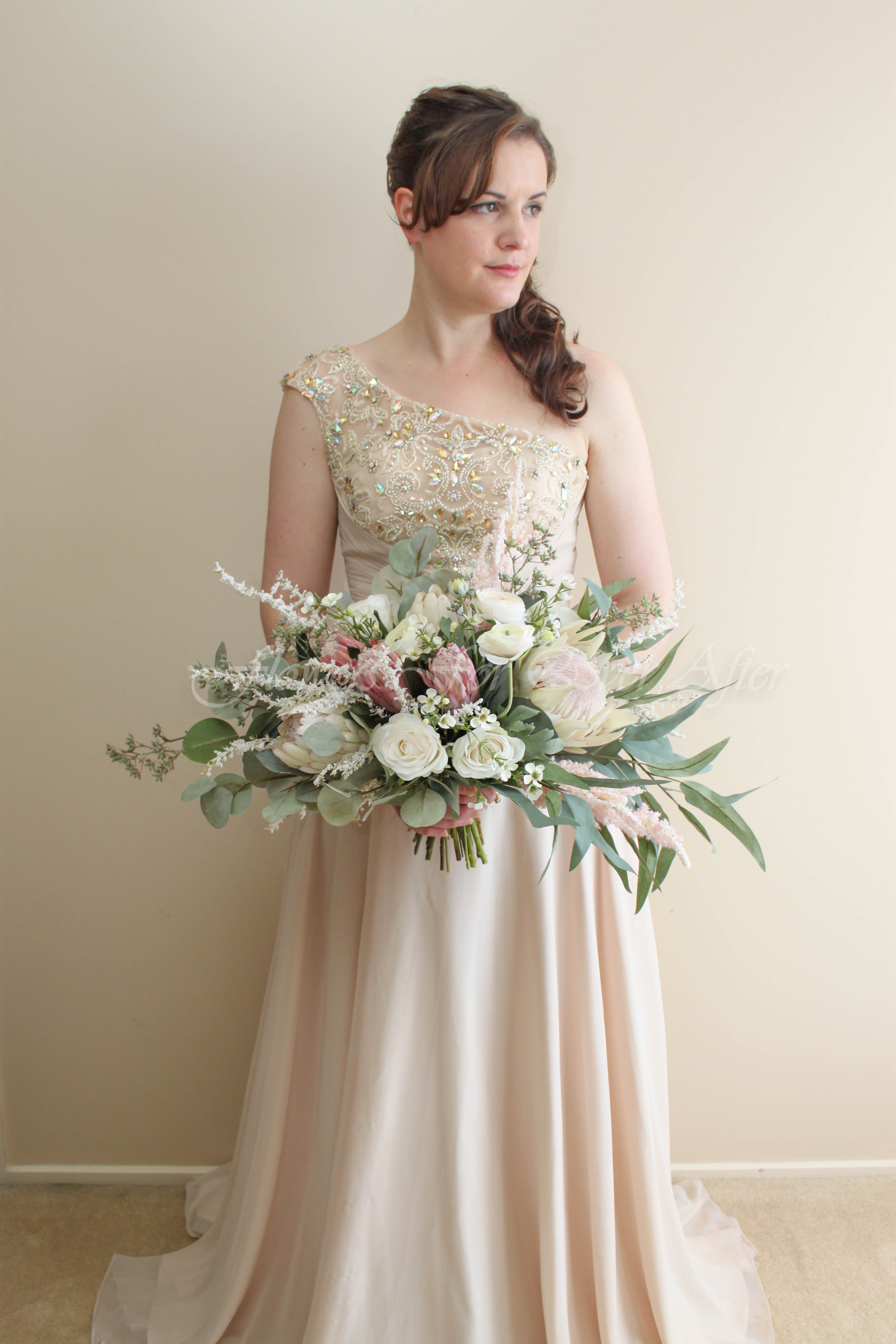 Silk Artificial bridal bouquet, stunning wedding flower design featuring faux protea, eucalyptus, roses, ranunculus, flowers. Arranged in a side sweeping loose garden posy style. Made in Melbourne Australia by Flowers For Ever After. Custom Designs welcome Worldwide shipping available.